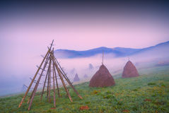 Haystacks in a misty valley Stock Photo