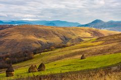 Haystacks on the rural fields. Lovely countryside scenery in mountains. distant mountain with snowy top under the overcast november sky stock photography