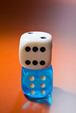 Hazard. Blue and white dice on a brown background Stock Images