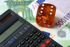 Hazard of business. Calculator with dice on money background royalty free stock image