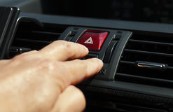 Hazard button. Hand pressing a hazard button, concept of safety on the roads royalty free stock photos