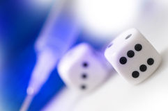 Hazard culd become an addiction. Dice and injection on a white background royalty free stock image
