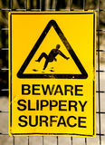 Hazard Sign: BEWARE SLIPPERY SURFACE with picture of man falling. Old, scratched and damaged yellow and black warning sign stating BEWARE SLIPPERY SURFACE with stock images