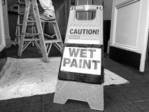 Hazard sign reads: Caution Wet Paint. Renovation and construction concept stock image