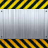Hazard Stripes Brushed Metal. A riveted 3d brushed metal plate on a construction hazard stripes background Stock Image