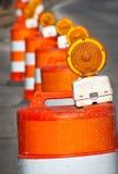 Hazard warning bollards. Receding line of warning, barrel shaped bollards with hazard lights Stock Photo