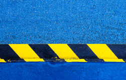 Hazard Warning Paint on Floor. Yellow and black hazard warning stripes painted on a metal rail on a blue floor stock image