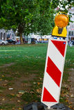 Hazard warning sign with solar light. Red and white striped hazard warning sign with solar light in a green urban square in a close up view with copy space royalty free stock photography