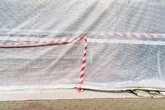 Hazard warning tape on construction site. Red and white strip on light fabric stock photo