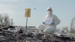 Hazardous area, Hazmat scientist into protective suit shows sign save the planet on junk yard with pointer biological stock footage