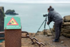 Hazardous cliff sign in Iceland. DYRHOLAEY, ICELAND - MAY 21, 2019: Photographer ignoring a hazardous cliff sign and passing over the fence in the prohibited royalty free stock photo