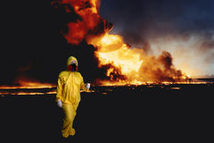 Hazardous Duty, Industrial Accident. Woman in a hazmat suit walking away from an oil well fire Stock Photography