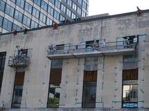 Hazardous Repairs. A work crew in hazardous materials suits repair a older building royalty free stock image