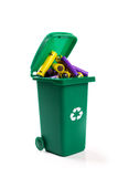 Hazardous waste recycling - green wheelie bin full with batterie. S. isolated on white Royalty Free Stock Photography