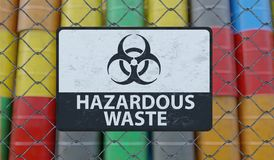Hazardous waste sign on chain link fence. Oil barrels in background. 3D rendered illustration.  Royalty Free Stock Image