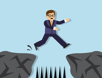 Hazards and risks in the business. Businessman jumps from one cliff to another. Between the cliffs sharp stakes Stock Image