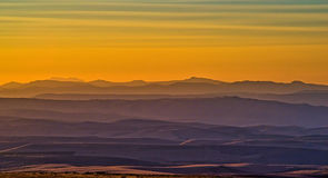 Haze in the Hills at Sunset. Haze from distant wildfires and dust kicked up by combines in the wheat fields combine to create soft layers of tones in the distant Royalty Free Stock Image