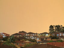Modern homes urban living by haze. Family homes in veil of haze with an extraordinary light reflected in the windows. Picture taken at bush-fires burning across royalty free stock photos