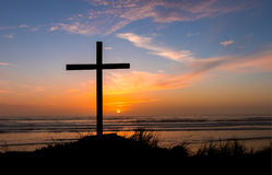 Haze Salvation Sunset Cross. Black cross on a beach with a haze sky sunset behind it Royalty Free Stock Photo
