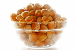 Hazel nut. S in glass bowl. Isolated over white background Royalty Free Stock Photography