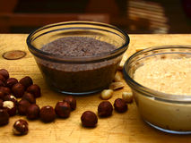 Hazel Nut Butter. Homemade hazel nut and peanut butters on a well-used rustic cutting board stock images