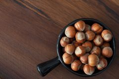 Hazel nuts in black bowl on wooden table. With free space royalty free stock images