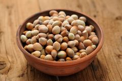 Hazel nuts in clay bowl. On wooden background Royalty Free Stock Photo