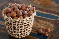 Hazel nuts in wicker busket on table. Hazel nuts in wicker busket on wooden table stock photo