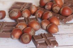 Hazelnoot en chocolade op houten achtergrond Stock Afbeeldingen