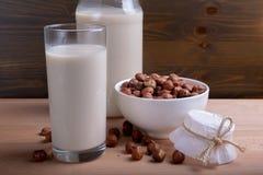 Hazelnootmelk in glas en organische hazelnoten op houten achtergrond, Alternatieve Melk stock afbeelding