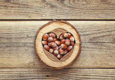 Hazelnut in a carved wooden heart on old wooden background. Top Stock Photography
