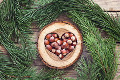 Hazelnut in a carved wooden heart and pine branches around on ol Royalty Free Stock Photography