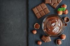 Hazelnut chocolate spread. Hazelnut spread with nuts and chocolate bar Stock Images