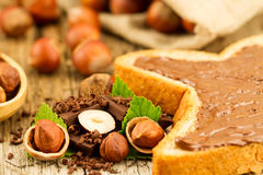 Hazelnut with chocolate, toast and green leaves on wooden background Stock Images