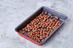 Hazelnut on cooking tray over white background, selective focus, shallow depth of field, top view. Hazelnut on cooking tray over white textured background stock images