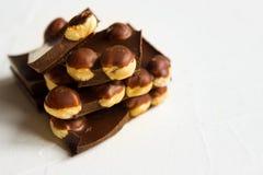 Hazelnut dark chocolate pieces tower on white background royalty free stock image