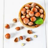Hazelnut dokrętki w drewnianym pucharze na białym drewnianym stole Superfood zdjęcie royalty free