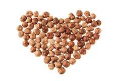Hazelnut heap in heart shape on white background. royalty free stock image