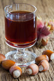 Hazelnut liqueur in a glass and hazelnuts Stock Images
