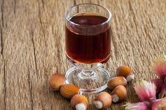 Hazelnut liqueur in a glass and hazelnuts Stock Photos