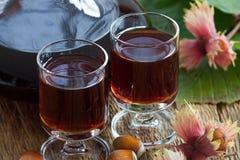 Hazelnut liqueur and hazelnuts Stock Photo