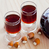 Hazelnut liqueur in two glasses and hazelnuts Stock Image