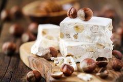 Hazelnut nougat or torrone. Delicious Italian festive torrone or nougat with hazelnuts on a wood Stock Photos
