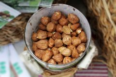 Heap of peeled organic raw hazelnuts in a metal bowl on bokeh background. Selective focus Royalty Free Stock Photography