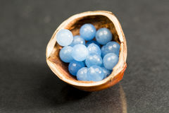 Hazelnut shell with small blue and transparent gemstones Stock Photos