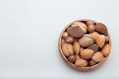 Hazelnut, walnut, almond and brazil nuts in wooden bowl, horizontal, copy space. Hazelnut, walnut, almond and brazil nuts in a wooden bowl, horizontal, copy stock photo
