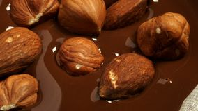 Hazelnuts and almonds fall into the melted chocolate. 4K, UHD, 3840x2160, Video, Clip stock photo