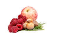 Hazelnuts,apple and raspberries on a white. Royalty Free Stock Images