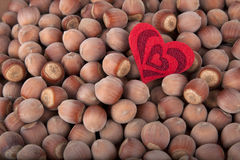 Hazelnuts background with a heart. Hazelnuts background with red heart Royalty Free Stock Photos