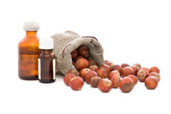 Hazelnuts in bag and bottles with oil. Royalty Free Stock Images